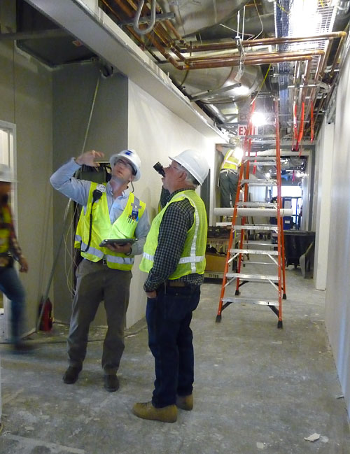 Commissioning specialist does a walk-through inspection of the Norman Hackerman Building.