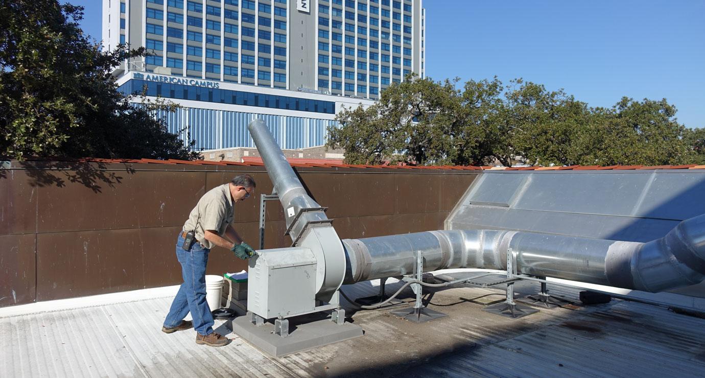 Maintenance crew member checking roof duct work - Maintenance Improvement Initiative