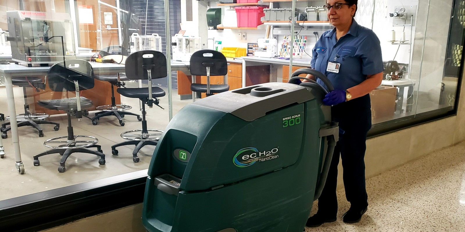 Image of Amal Abraham (Custodial Services) using a floor scrubber