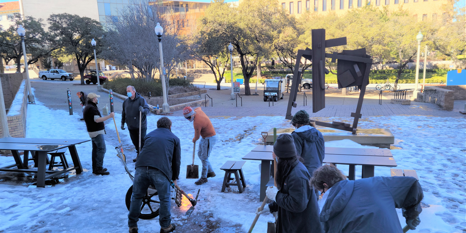 Image of Landscape Services staff using shovels and a propane torch to remove ice at PCL