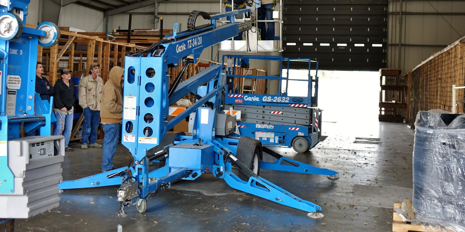 employees operating and observing aerial lift in use in garage